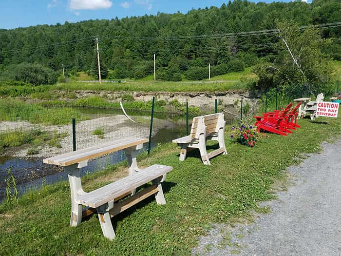 outdoor seating along river at Copper Plate in Barton VT