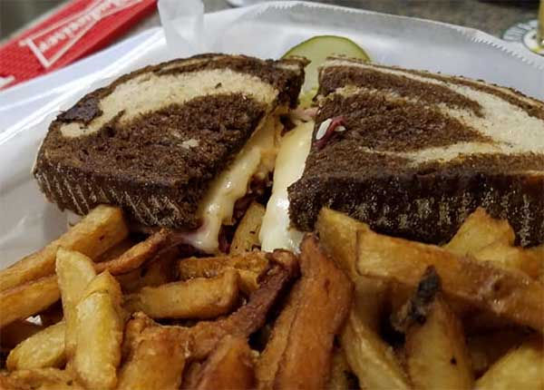 Reuben on rye in take out container from The Warehouse in Newport, VT