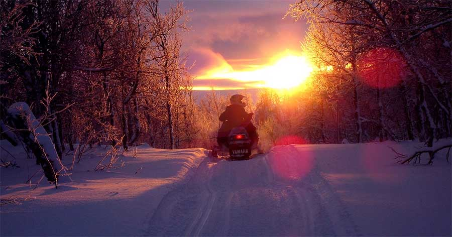 snowmobile winter fun in Vermont with sunset